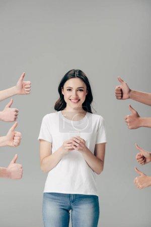 abgeschnittene Ansicht von Männern und Frauen, die Daumen nach oben zeigen in der Nähe eines glücklichen Mädchens mit Smartphone isoliert auf grau