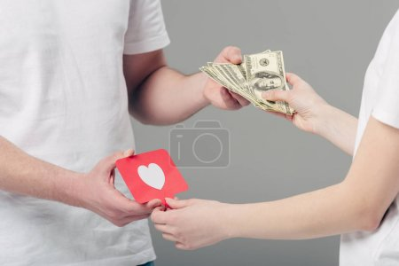 partial view of man giving dollar banknotes to woman holding red paper cut card with heart symbol isolated on grey