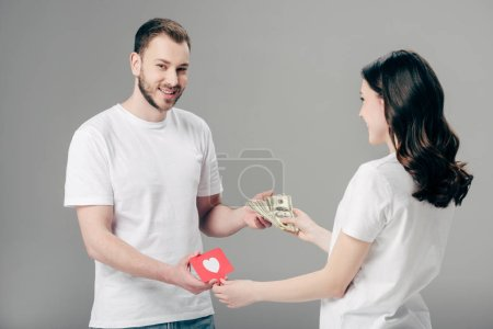 smiling handsome man giving dollar banknotes to young woman with red paper cut card with heart symbol on grey background