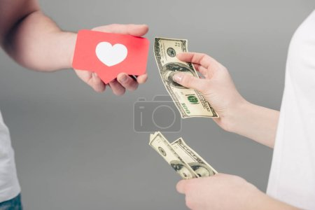 cropped view of woman giving dollar banknotes to man with red paper cut card with heart symbol on grey background