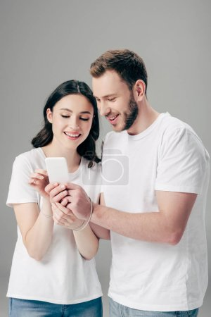 Photo for Cheerful man and woman in white t-shirts with usb cable around hands using smartphone isolated on grey - Royalty Free Image