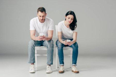 Photo pour Homme et femme concentrés dans les t-shirts blancs et les jeans s'asseyant sur des chaises et utilisant des smartphones sur le fond gris - image libre de droit