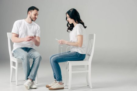 Photo for Concentrated man and woman in white t-shirts and blue jeans sitting on chairs and using smartphones on grey background - Royalty Free Image