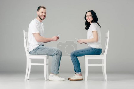 Photo for Smiling man and woman in white t-shirts and blue jeans sitting on chairs and using smartphones on grey background - Royalty Free Image