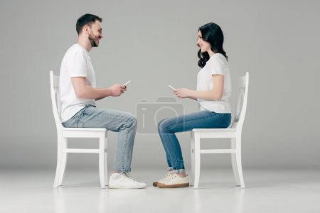 Photo for Side view of smiling man and woman in white t-shirts and blue jeans sitting on chairs with smartphones and looking at each other on grey background - Royalty Free Image
