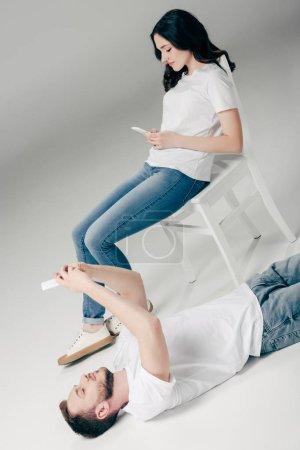 Photo pour Jolie jeune femme s'asseyant sur la présidence et utilisant le smartphone près de l'homme beau se trouvant sur l'étage et prenant le selfie sur le fond gris - image libre de droit