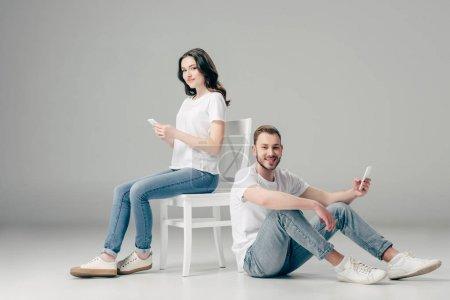 Photo pour Femme de sourire utilisant le smartphone près de l'homme gai s'asseyant sur l'étage avec le smartphone sur le fond gris - image libre de droit