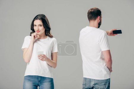 Photo for Smiling attractive girl in white t-shirt standing near young man taking selfie with smartphone isolated on grey - Royalty Free Image