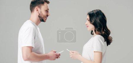 Photo pour Photo panoramique de jeune homme et femme regardant l'un l'autre tout en tenant des smartphones isolés sur le gris - image libre de droit
