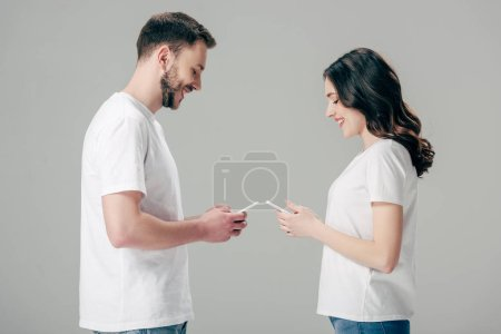 Photo for Side view of smiling young man and woman in white t-shirts using smartphones isolated on grey - Royalty Free Image