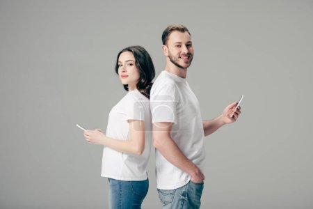 Photo for Young smiling man and woman in white t-shirts standing back to back and using smartphones isolated on grey - Royalty Free Image