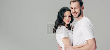 Photo for Panoramic shot of happy young couple embracing and looking at camera isolated on grey - Royalty Free Image