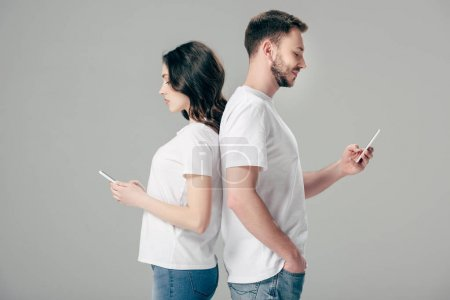 Foto de Focused man and woman in white t-shirts standing back to back and using smartphones isolated on grey - Imagen libre de derechos