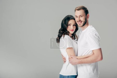 Photo for Smiling young couple in white t-shirts embracing and looking at camera isolated on grey - Royalty Free Image