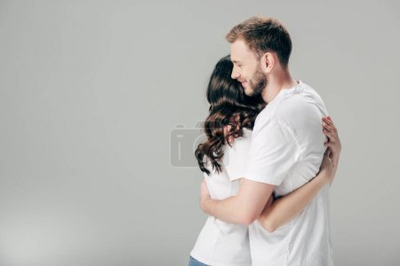 Photo for Happy young couple in white t-shirts embracing on grey background - Royalty Free Image