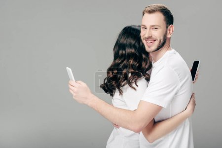 Photo pour Young couple in white t-shirts hugging while using smartphones on grey background - image libre de droit