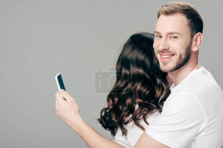 Photo for Handsome smiling man embracing woman and using smartphone isolated on grey - Royalty Free Image