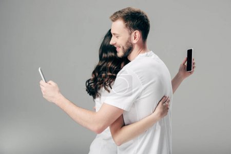 Photo for Young couple in white t-shirts hugging while using smartphones on grey background - Royalty Free Image