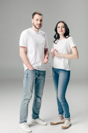 Photo for Young man and woman in white t-shirts and blue jeans looking at camera on grey background - Royalty Free Image