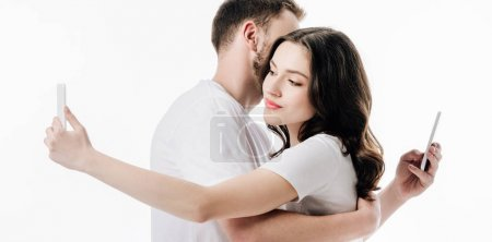 Photo for Panoramic shot of young couple embracing while using smartphones isolated on white - Royalty Free Image