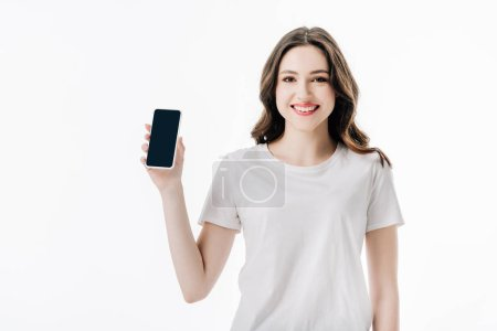 Photo for Beautiful cheerful girl in white t-shirt holding smartphone with blank screen and looking at camera isolated on white - Royalty Free Image