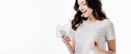 Photo pour Plan panoramique de jolie fille gaie en t-shirt blanc en utilisant smartphone isolé sur blanc - image libre de droit