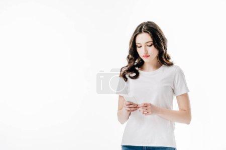 Photo pour Jeune femme concentrée dans le t-shirt blanc utilisant le smartphone isolé sur le blanc - image libre de droit