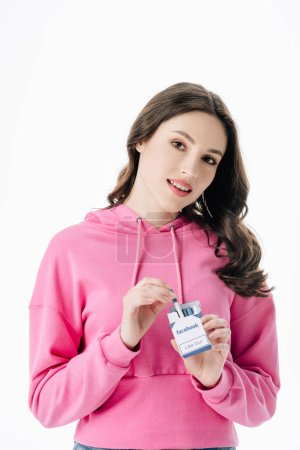 Photo for Attractive smiling girl in pink hoodie getting cigarette from pack with facebook logo isolated on white - Royalty Free Image