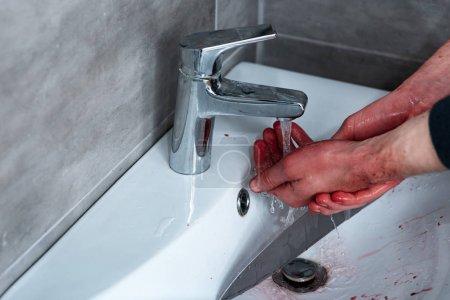Foto de Vista parcial del hombre lavando las manos sangrantes en el fregadero - Imagen libre de derechos