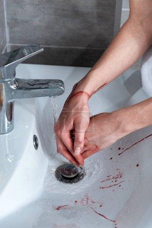 Foto de Vista parcial de la mujer lavarse las manos sangrando en el baño - Imagen libre de derechos