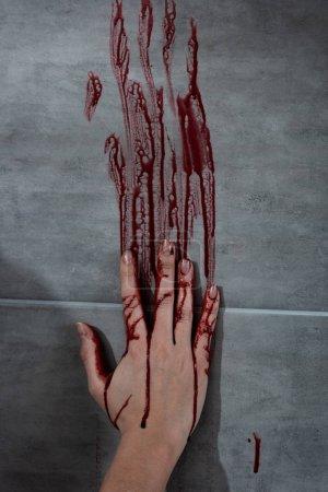 Foto de Mano sangrante e huella de sangre en la pared gris - Imagen libre de derechos