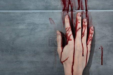 Photo pour La main saignante et l'empreinte de sang sur le mur gris - image libre de droit