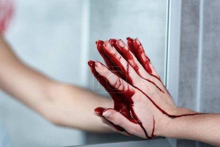 Foto de Vista parcial de la mujer con la mano sangrando tocando espejo en el baño - Imagen libre de derechos