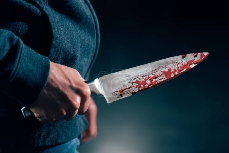 Photo for Cropped view of murderer holding knife in blood - Royalty Free Image
