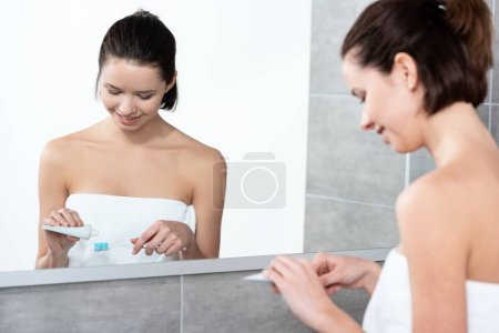 Photo pour Young woman applying toothpaste on toothbrush near mirror in bathroom - image libre de droit