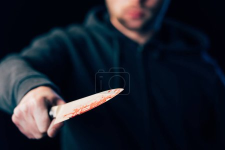 Photo for Selective focus of killer holding knife isolated on black - Royalty Free Image