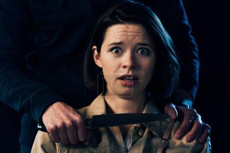 Photo pour Vue partielle de la femme d'attaque criminelle avec le couteau isolé sur le noir - image libre de droit