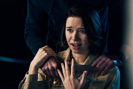 Photo for Partial view of criminal attacking woman with knife on black - Royalty Free Image
