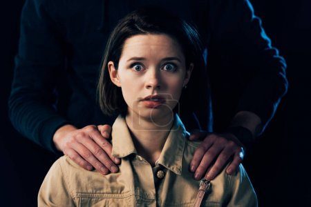 cropped view of criminal attacking scared woman isolated on black