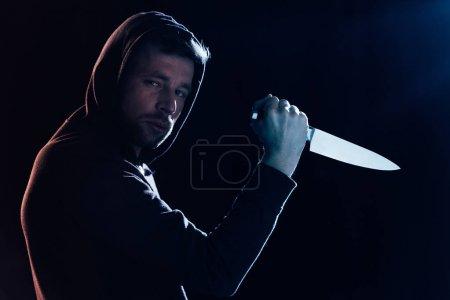 Photo pour Criminel en vêtements décontractés tenant couteau et regardant la caméra sur noir - image libre de droit
