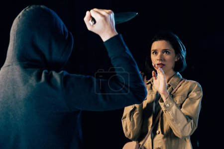 Photo for Partial view of criminal attacking woman with knife isolated on black - Royalty Free Image