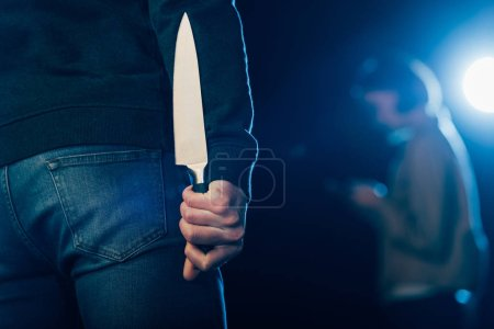 Photo for Cropped view of murderer hiding knife behind back on black - Royalty Free Image