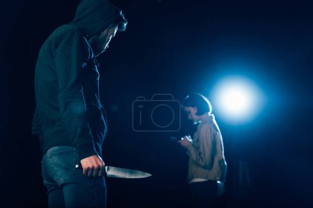 Photo for Killer in hood holding knife and looking at woman on black - Royalty Free Image
