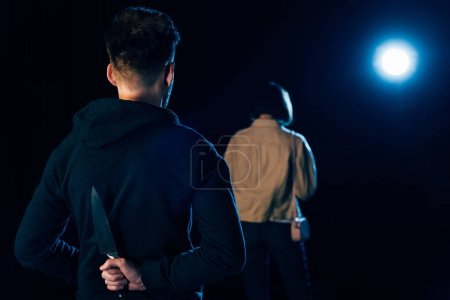 Photo for Back view view of murderer hiding knife and looking at victim on black - Royalty Free Image