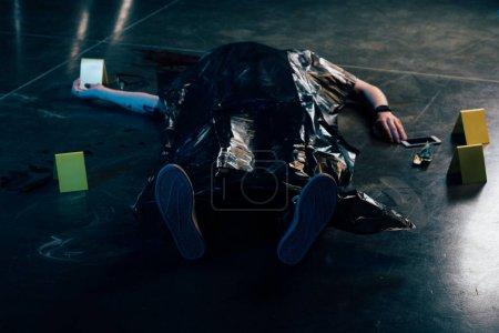 Photo pour Cadavre couvert près des preuves sur le sol sur les lieux du crime - image libre de droit
