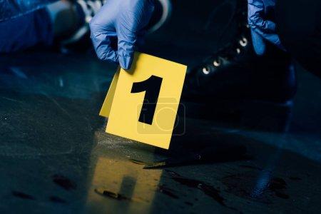 Photo pour Vue partielle de l'enquêteur dans des gants de caoutchouc avec marqueur de preuve sur les lieux du crime - image libre de droit