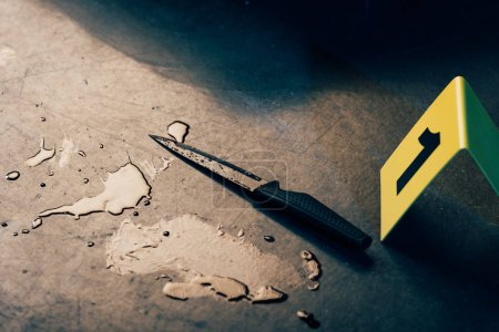 Photo for Knife, evidence marker and blood stains at crime scene - Royalty Free Image