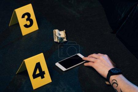 Photo pour Vue partielle du cadavre couvert avec smartphone et billet en dollars sur les lieux du crime - image libre de droit