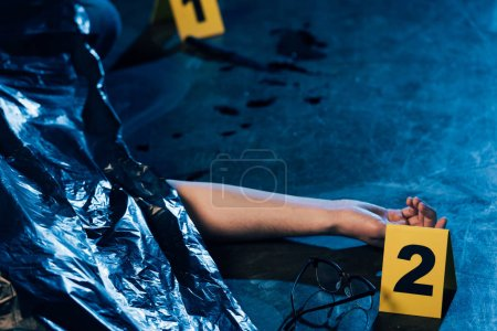 Photo for Partial view of covered corpse with glasses at crime scene - Royalty Free Image