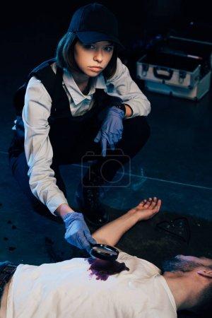 Photo pour Enquêteur assis près du cadavre et utilisant une loupe sur les lieux du crime - image libre de droit